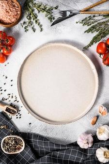 Biały pusty talerz pośrodku pomidorów i ziół