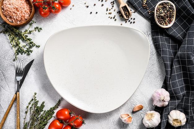 Biały pusty talerz pośrodku przypraw i składników