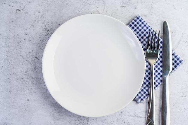 Biały pusty talerz z widelcem i nożem na niebiesko-białym obrusie.