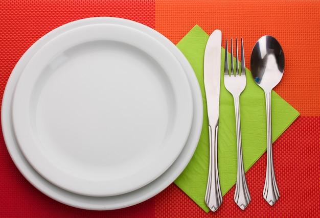 Biały pusty talerz z widelcem, łyżką i nożem na czerwonym obrusie