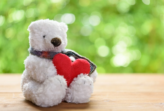 Biały puszysty miś zabawka przytulanie czerwone serce siedzi samotnie na drewnianym stole