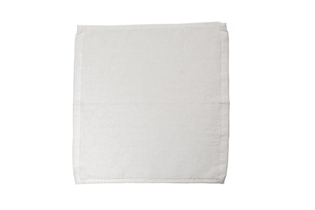 Biały puszysty ręcznik bawełniany na białym tle na białej powierzchni. uzdrowisko i ośrodek.
