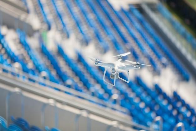 Biały quadkopter leci nad stadionem piłkarskim.