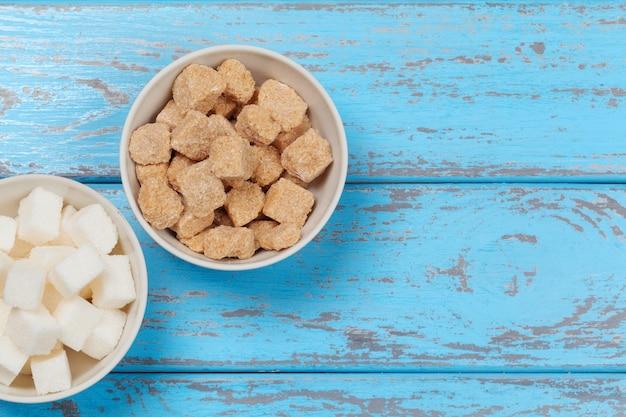 Biały rafinowany cukier i brązowe nierafinowane kostki cukru
