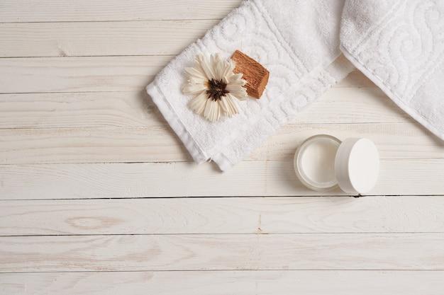 Biały ręcznik kosmetyki akcesoria łazienkowe stół drewniany.