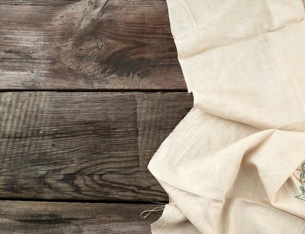 Biały ręcznik tekstylny kuchenny złożony na szarym drewnianym stole