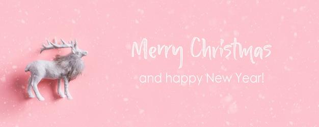 Biały renifer na różowym tle. wesołych świąt i szczęśliwego nowego roku banner