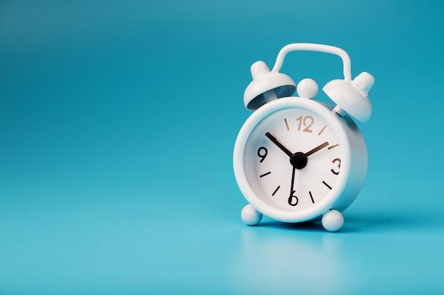 Biały retro budzik na niebieskim tle. pojęcie czasu z wolnego miejsca na tekst.