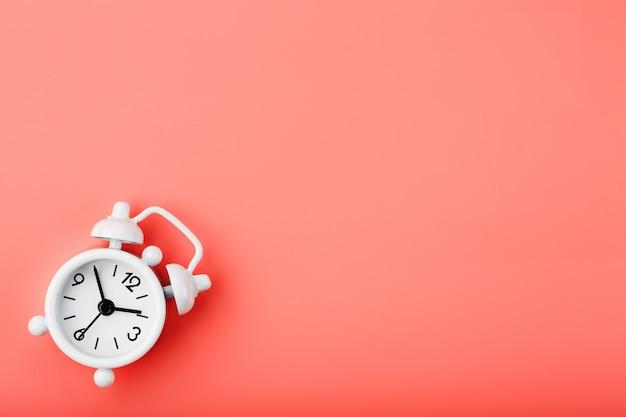 Biały retro budzik na różowym tle. pojęcie czasu z wolnego miejsca na tekst.