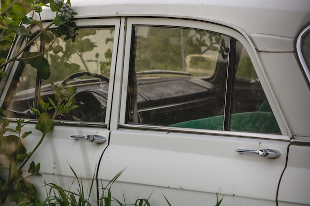 Biały retro samochód na stronie w trawie. drzwi samochodowe.