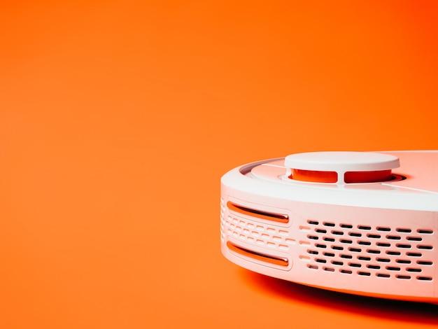 Biały robota odkurzacz odizolowywający na pomarańczowym tle.