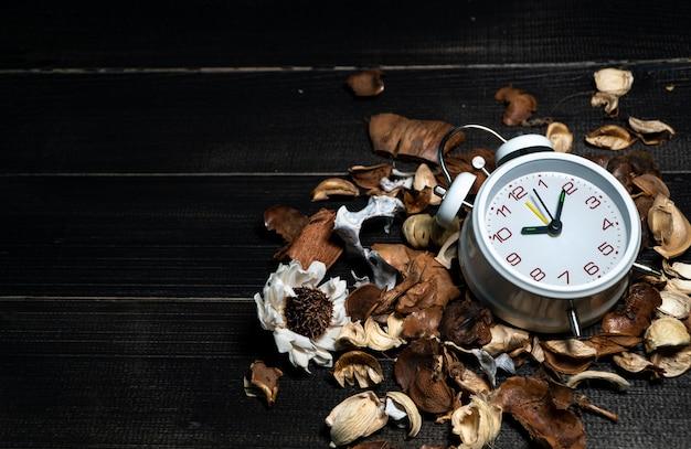 Biały rocznika zegar stawiający na wysuszonych liściach na drewnianym retro czerń stole
