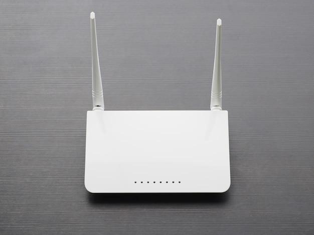 Biały router bezprzewodowy na stole z ciemnego drewna.