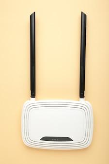 Biały router wi-fi z czarnymi antenami na beżowej powierzchni z miejscem na kopię