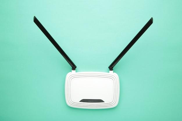 Biały router wi-fi z czarnymi antenami na miętowej powierzchni z miejscem na kopię