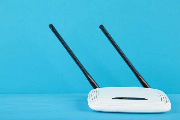 Biały router wi-fi z czarnymi antenami na niebieskiej powierzchni z miejscem na kopię