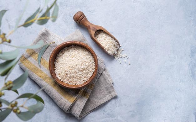 Biały ryż arborio w drewnianej misce na serwetce