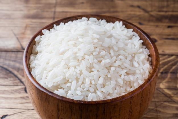 Biały ryż grysuje w drewnianej misce na rustykalnym drewnianym stole.
