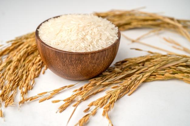 Biały ryż jaśminowy w drewnianej misce ze złotym ziarnem z gospodarstwa rolnego.