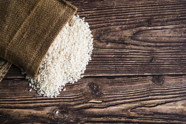 Biały ryż rozrzucony od worka na stole