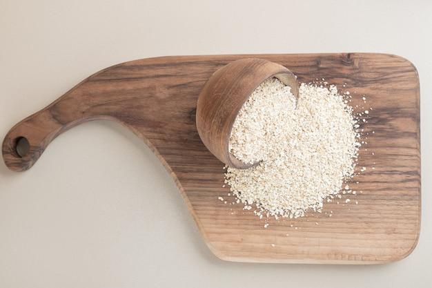 Biały ryż w drewnianej filiżance na drewnianym talerzu.