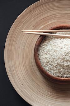 Biały ryż w drewnianej misce z drewnianymi pałeczkami
