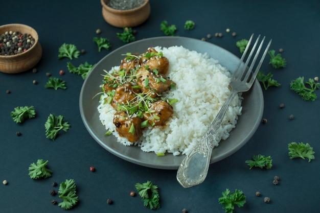 Biały ryż z mięsem, przyozdobiony natką pietruszki. azjatyckie jedzenie. paluszki spożywcze. miejsce na tekst.