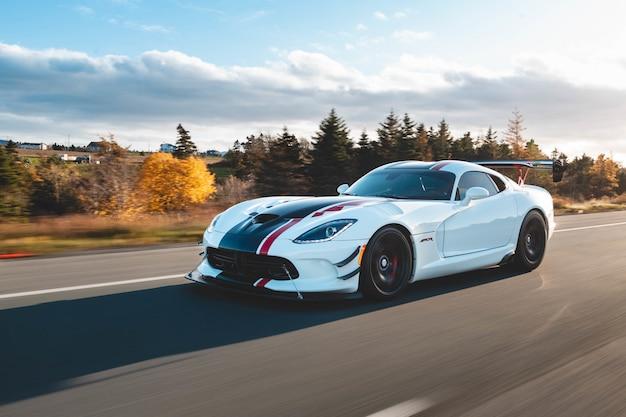 Biały samochód coupe jazdy na drodze