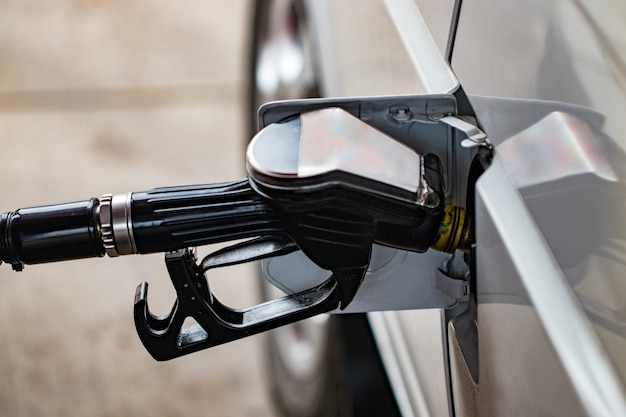 Biały samochód jest tankowany na stację benzynową, pistolet do tankowania w szyjce wlewu cysterny benzynowej.