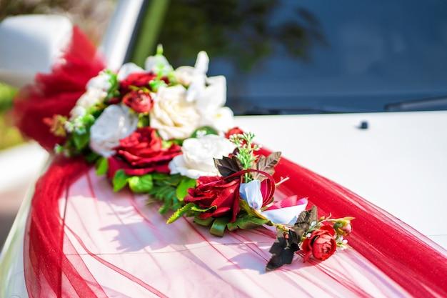 Biały samochód ślubny ozdobiony świeżymi kwiatami. dekoracje ślubne