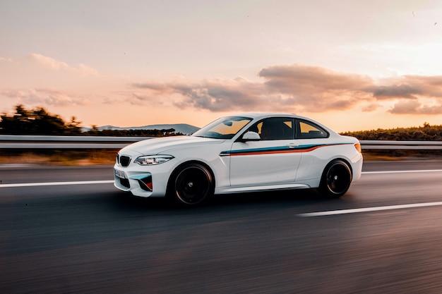 Biały samochód sportowy z pasami autotuningu na drodze.