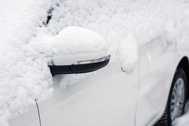 Biały samochód w śniegu, zbliżenie lusterko boczne