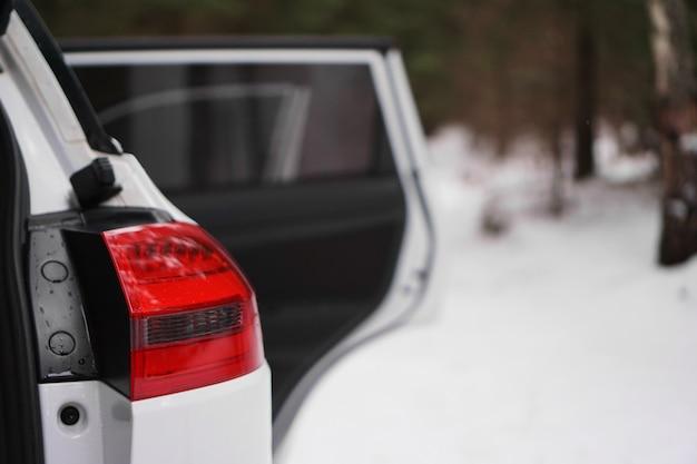 Biały samochód z czerwonym reflektorem i otwartymi drzwiami w zimowym lesie