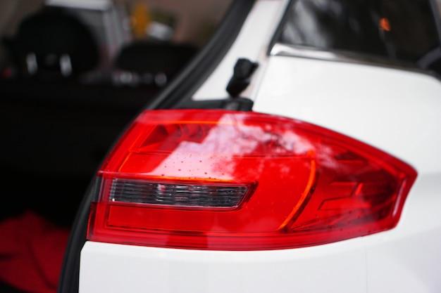 Biały samochód z czerwonym reflektorem i otwartymi drzwiami