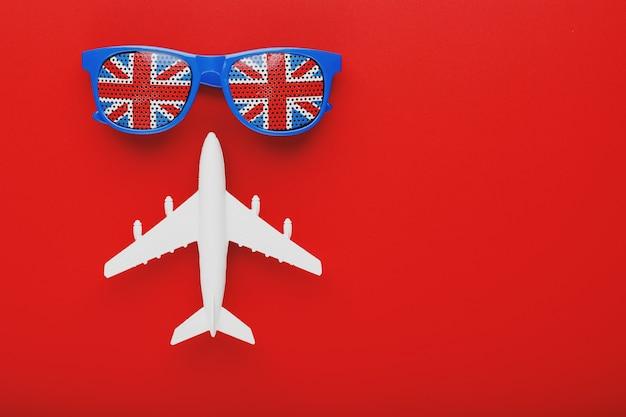 Biały samolot i okulary przeciwsłoneczne z flagą wielkiej brytanii. podróż do anglii.