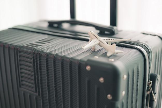 Biały samolot model na czarnym bagażu dla podróży i podróży pojęcia