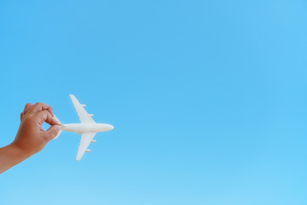 Biały samolot w dłoni dziecka na błękitnym niebie
