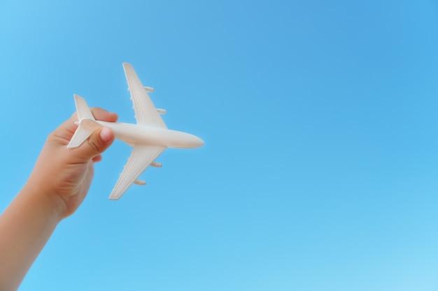 Biały samolot w dłoni dziecka na tle błękitnego nieba.