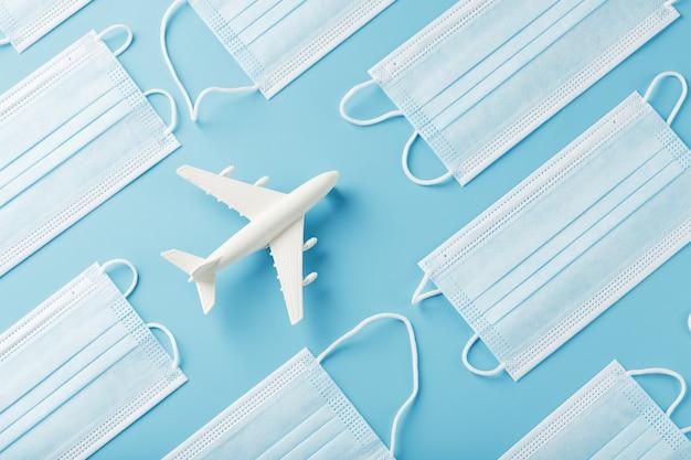 Biały samolot wokół masek ochronnych na niebieskiej powierzchni