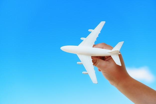 Biały samolot zabawka w dłoni dziecka na tle błękitnego nieba.