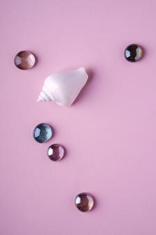 Biały seashell z błyszczącymi szklanymi kolorowymi marmurami na miękkiej części różowym tle, odgórny widok