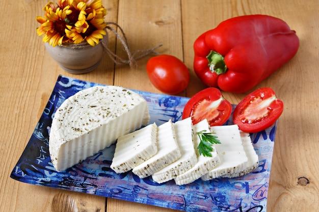 Biały ser, pomidory i pieprze na błękitnym talerzu na drewnianym tle ,.