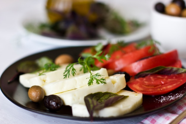 Biały ser z pomidorami, zielonymi i czarnymi oliwkami, bazylią, kolendrą i oliwą z oliwek