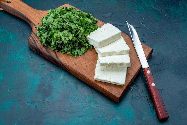 Biały ser ze świeżymi zieleniami na ciemnoniebieskim tle.