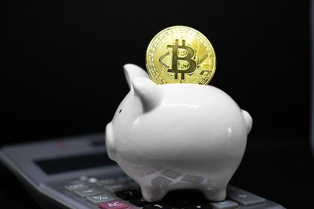 Biały skarbonka i złoty bitcoin na czarnym tle do oszczędzania bogactwa pieniędzy i koncepcji finansów oraz copyspace do projektowania.