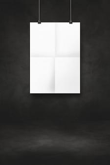 Biały składany plakat wiszący na czarnej ścianie z klipsami. pusty szablon makiety