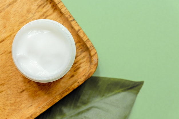 Biały słoik kremu do twarzy na drewnianej tacy. zielone tło, widok z góry, tropikalne liście. koncepcja kosmetyków naturalnych i spa.