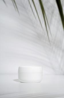 Biały słoik kremu na białym tle z tropikalnymi liśćmi palm i ich cieniem