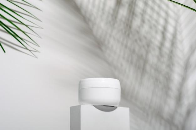 Biały słoik z kremem na stojaku na białym z tropikalnymi liśćmi palm i ich cieniem.