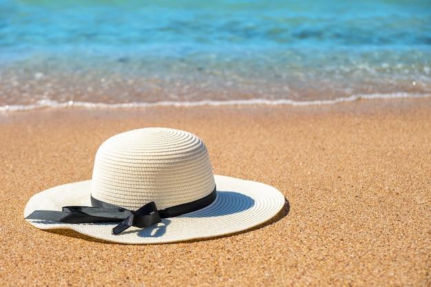 Biały słomiany kapelusz kłaść na tropikalnej piasek plaży